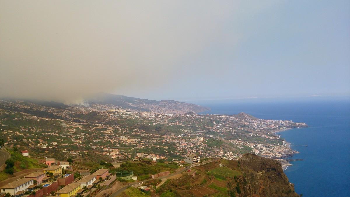 Blick auf Funchal und einen qualmenden Brandherd oberhalb Funchals